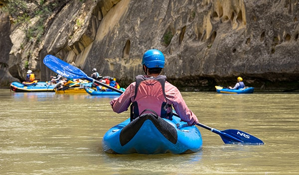 Students in kayaks on a river with FLOW